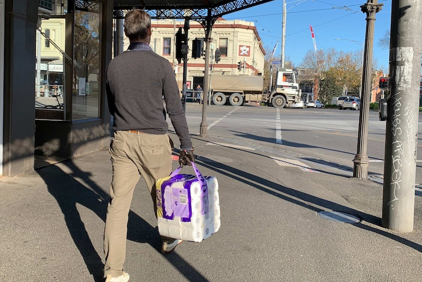 A man walks on the footpath holding a pack of toilet paper on a sunny day.