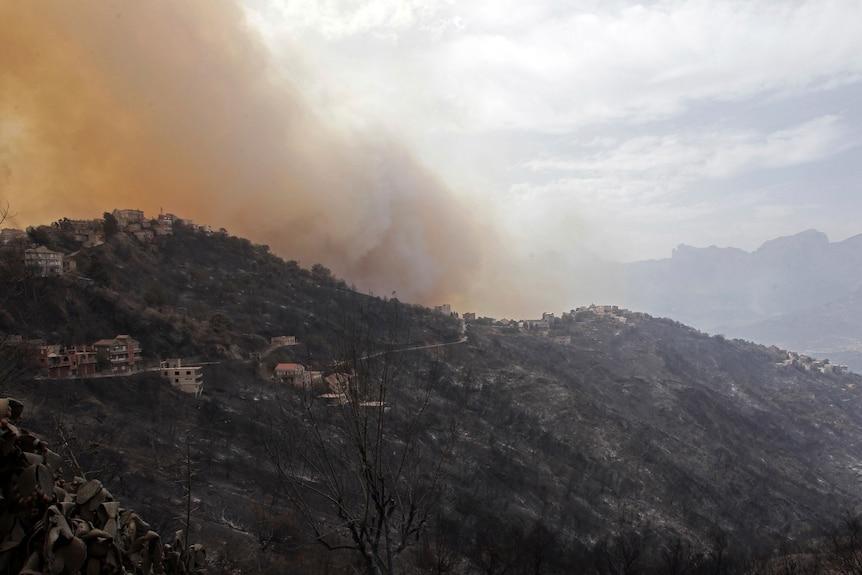 Большой дым и пожар на гористой местности.