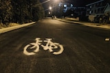 A white bike priority marking spray painted on Rutland Avenue in Victoria Park in Perth.