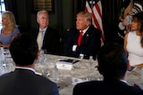 Donald Trumps speaks with his arms folded while sitting at a table flanked by Melania Trump and Tom Price.