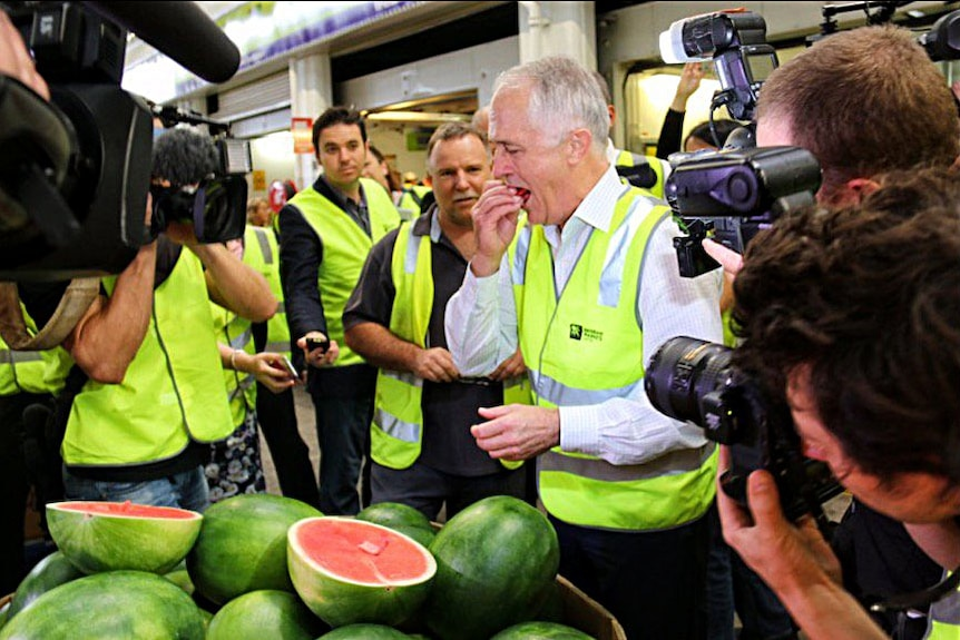 Side on view of Malcolm Turnbull eating some watermelon with a large crate of watermelons in the foreground.