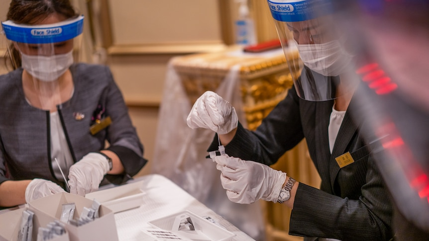 Two women in masks and shields put nasal swabs in testing vials in a hotel lobby