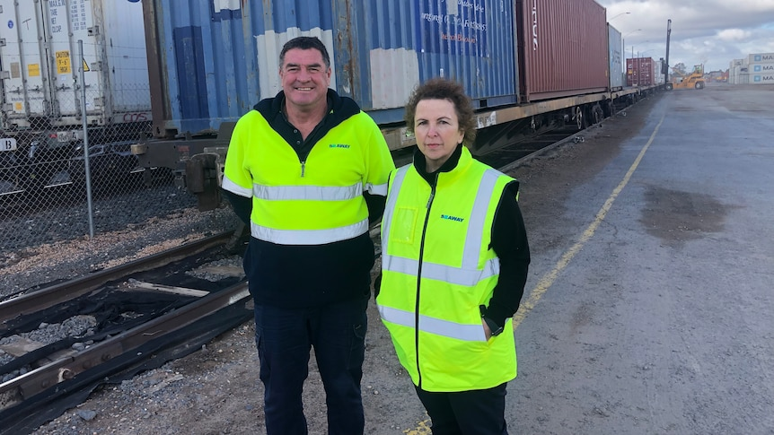 A man and a lady wearing hi vis jackets stand beside a train that's being loaded and unloaded