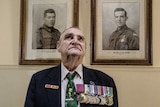 A man in his eighties, wearing his medals, standing in front of black-and-white framed photos of servicemen