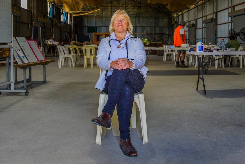 A woman with blonde hair and gold earrings sits on a plastic chair smiling in a large shed.