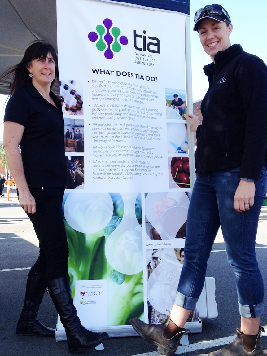 Dr Lyndal Mellefont and Dr Fiona Kerslake sporting boots in front of a Tasmanian Institute of Agriculture banner at the farmers