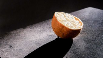 A shard of light shines on half a lemon.