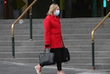A woman wearing a red coat and surgical mask, who is carrying a computer bag, walks past Flinders Street Station.