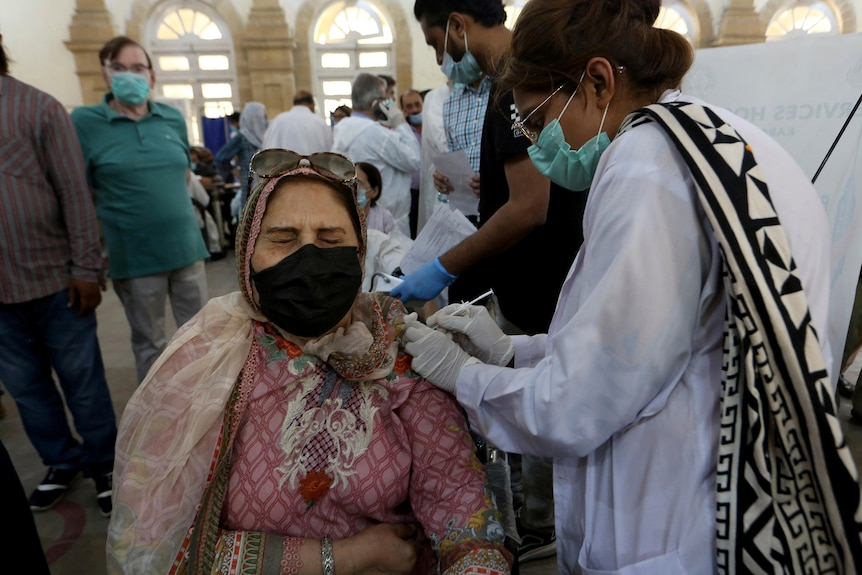 A woman wearing a pink headscarf and mask reacts while receiving a Sinopharm coronavirus vaccine from a health worker.