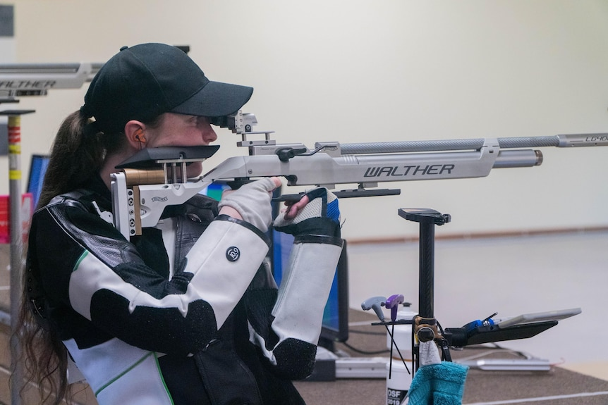 Elise Collier holds a rifle on her shoulder and aims down the sights