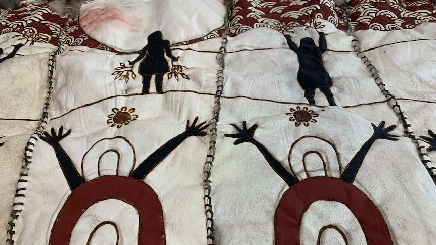 Women figures on possum skin cloak