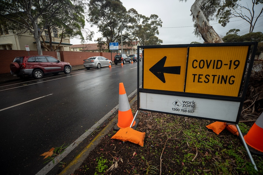 A sign saying COVID-19 testing on a road with cars parked next to it