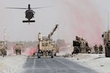 A military helicopter hovers over a road above other heavy machinery next to a damaged military vehicle.