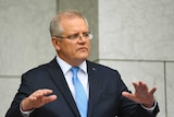 Australian Prime Minister Scott Morrison raises his hands while speaking at a press conference wearing a suit and blue tie