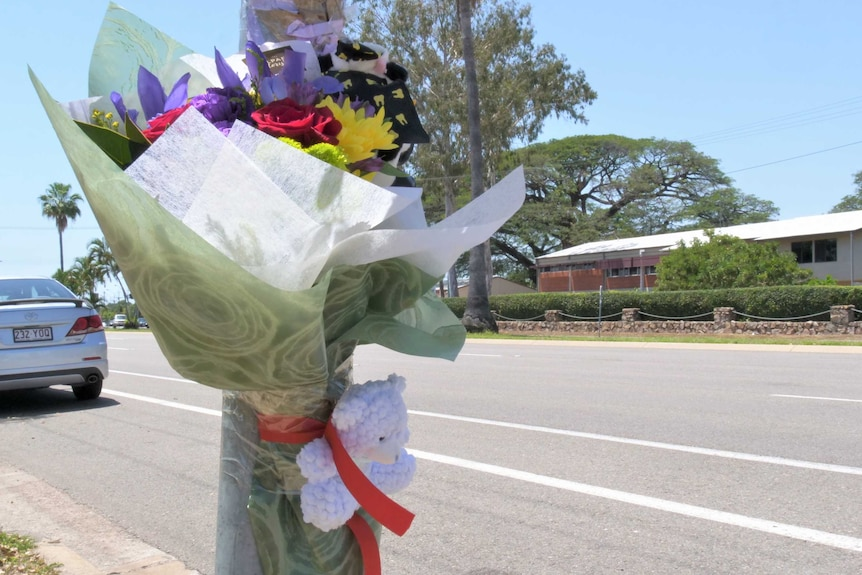 Colourful flowers and a small white teddy are taped to a light pole, next to a road
