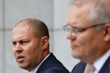 Josh Frydenberg and Scott Morrison stand behind podia in a marble-walled courtyard