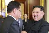 Kim Jong-un smiles as he shakes hands with a South Korean official.