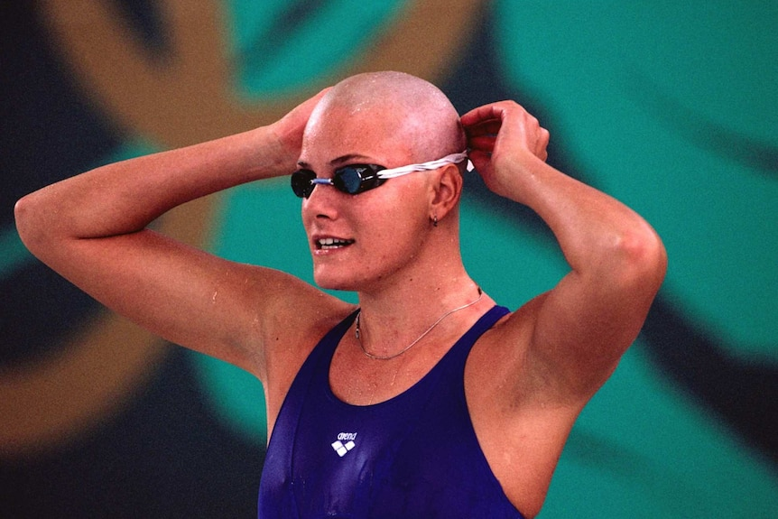 A female swimmer with a shaved head puts on her goggles before a race.