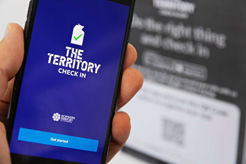 Fingers holds a mobile phone which displays a blue screen with white words that say The Territory Check In.