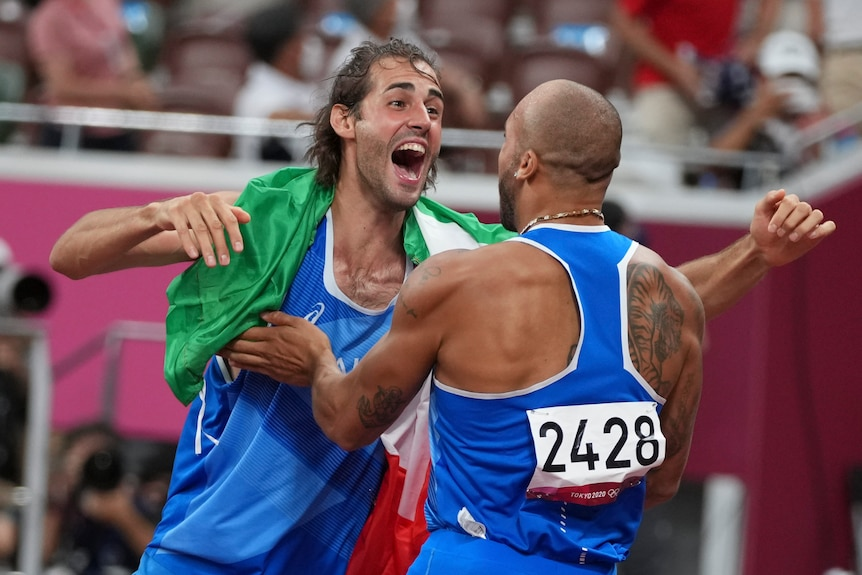 Italy's Gianmarco Tamberi (left) hugs countryman Lamont Marcell Jacobs after they won high jump and 100m gold.