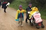 Refugees walk down a muddy rural road.