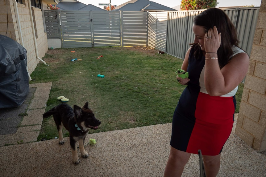 Woman (Natasha Turfrey) in backyard with dog and dog toys scattered in background.