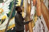 Street artist on a lift paints side of a silo