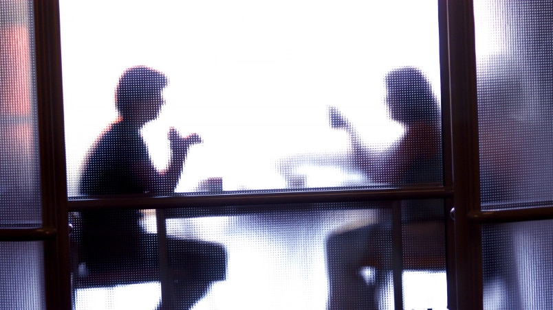 Two people obscured by opaque glass, sit at table.