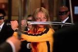A scene from the movie Kill Bill where Uma Thurman holds a sword.