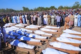 Hundreds of people gather outside around bodies wrapped in wide cloth.