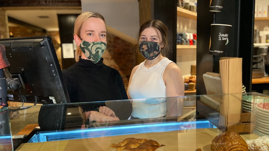 Paige and Rebecca stand together, with masks on, behind a cafe bench filled with focaccias and pastries.