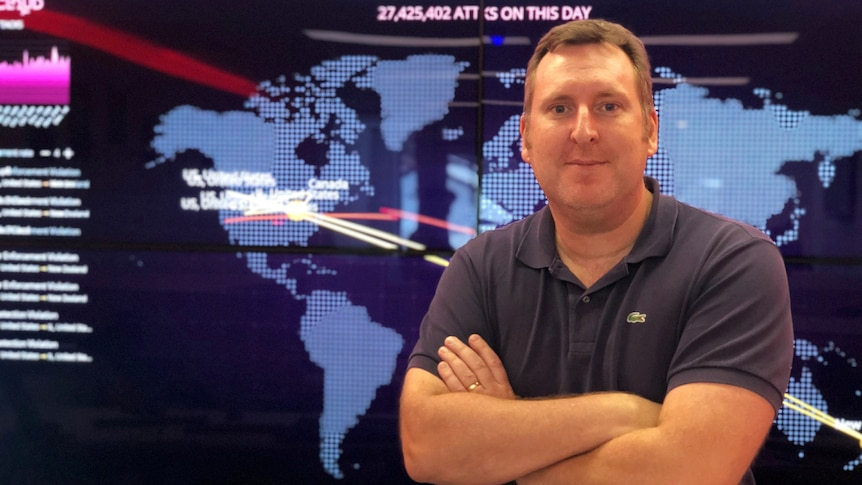 A man stands in front of a screen with a map of the world, his arms are crossed and he looks stern