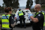 A police officer secures the rear door of a police van as two other officers look on.