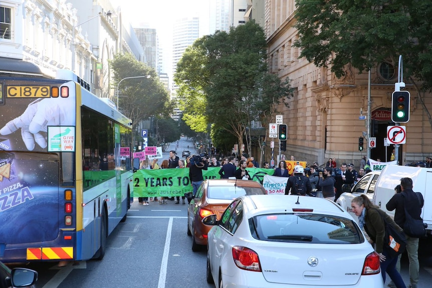 A couple dozen of protesters stand in the middle of the street in Brisbane's city.