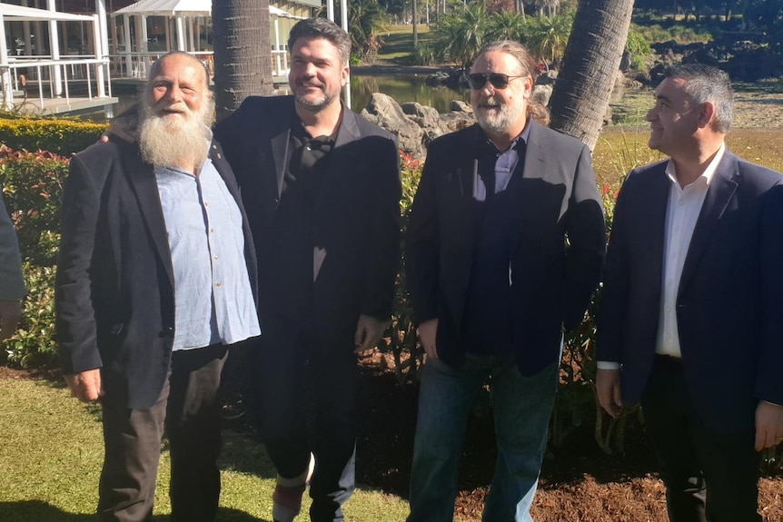 Russell Crowe stands with a group of men