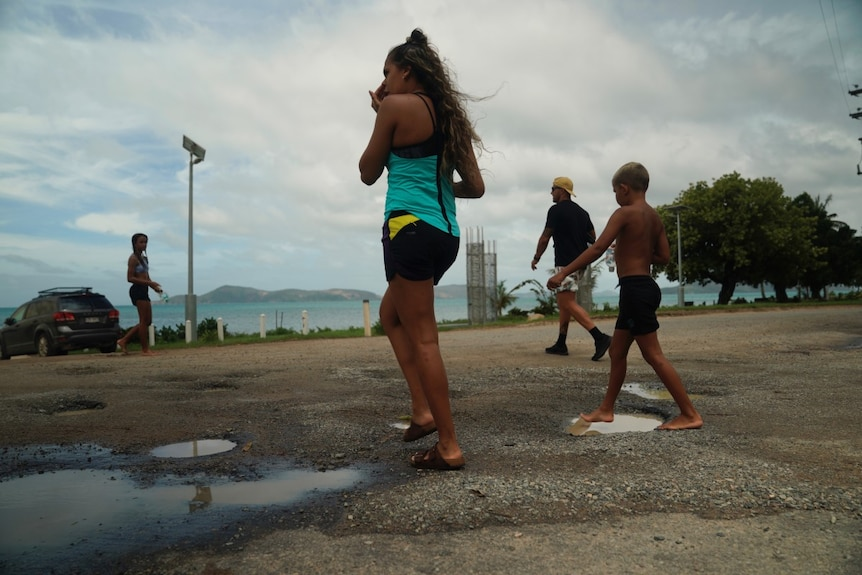 Children cross the road and walk towards the beach on Palm Island, North Queensland.