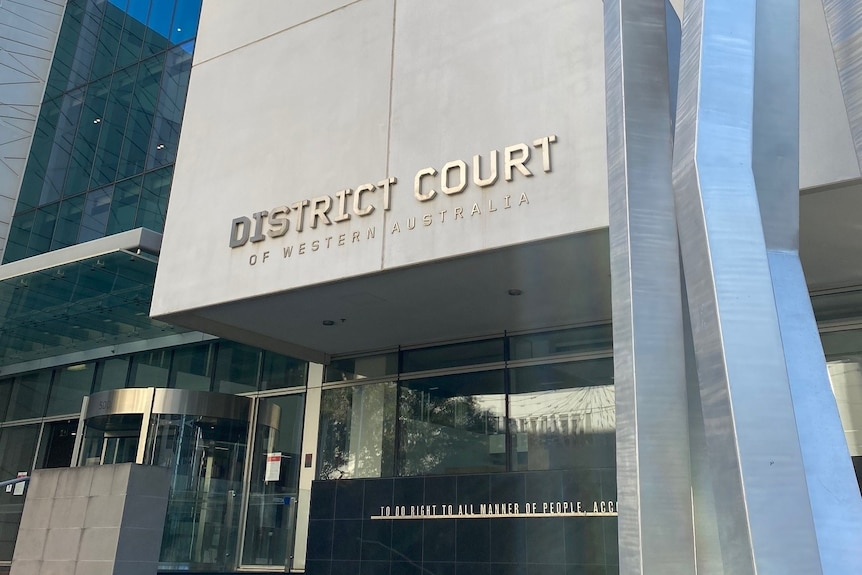 The exterior of the WA District Court building, with signage and glass doors, with steel artwork out the front.