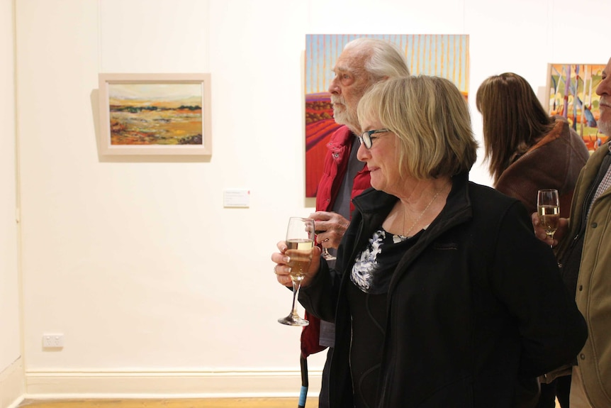 A woman with short blonde hair smiles at a painting at the Pro Hart Outback Art Prize exhibition.