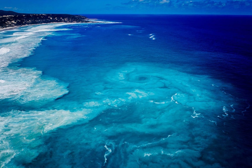 An aerial shot of a strikingly blue sea with a huge vortex out past the breakers.