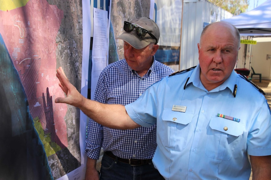 Two men inspect a map on a wall showing the extent of a fire ground
