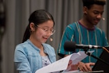 Teenage girl looking at script and talking into microphone with teenage boy in background.