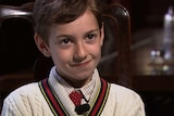 A young boy in a shirt, tie and jumper sits in a chair.