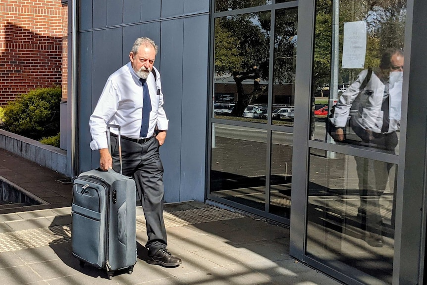 An elderly man looks at the camera as he enters court carrying a suitcase.