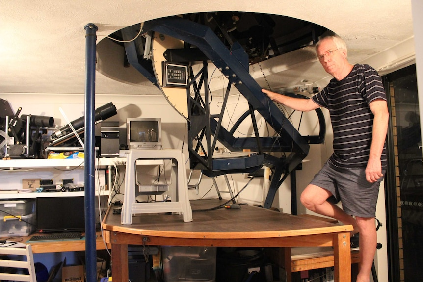 John Broughton stands under his homemade telescope, built into a dome on the side of his house in Reedy Creek, Queensland.