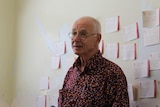 Dr Karl Kruszelnicki stands in front of a memory board