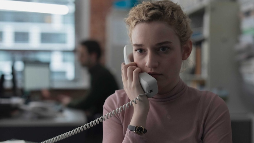 The actor Julia Garner in the film The Assistant, she's wearing a pink top, blonde hair, holding a landline phone up to her ear