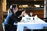 A woman looks at her smart phone in a restaurant