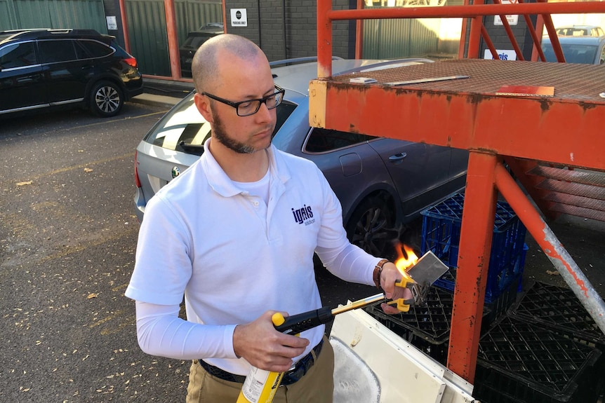 Man putting a torch to a square of metal.