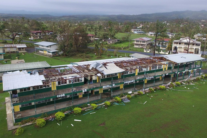 Aerial photo showing the roof missing off a primary school building housing several classrooms.