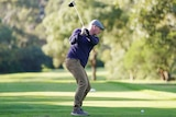 A male golfer takes a swing on a fairway at Brighton Golf Course in Melbourne.